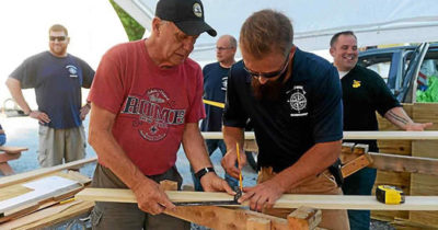 Two members of our workshop measuring wood to build into a kayak