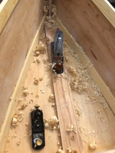 Shavings collect in the hull from planing the wood.